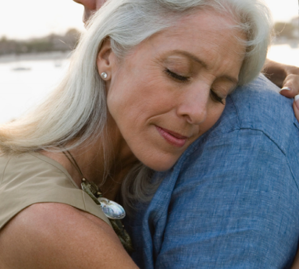 Woman with gray hair hugs man in denim shirt with lake in background.