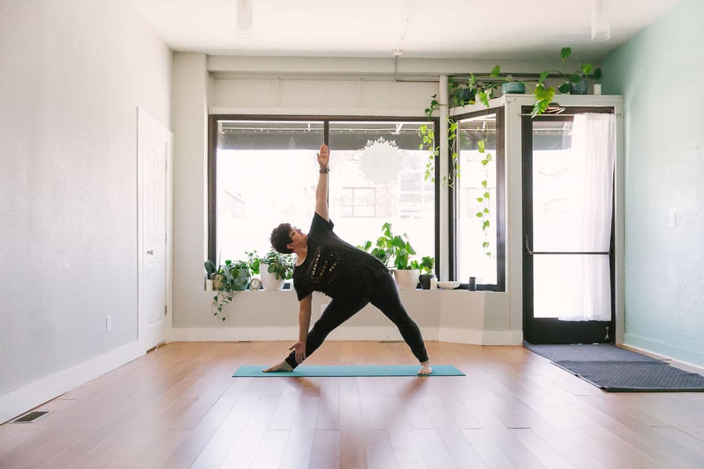 Rachel Holdgrafer, RYT 200, a plus-size yoga teacher, demonstrates extended triangle pose.