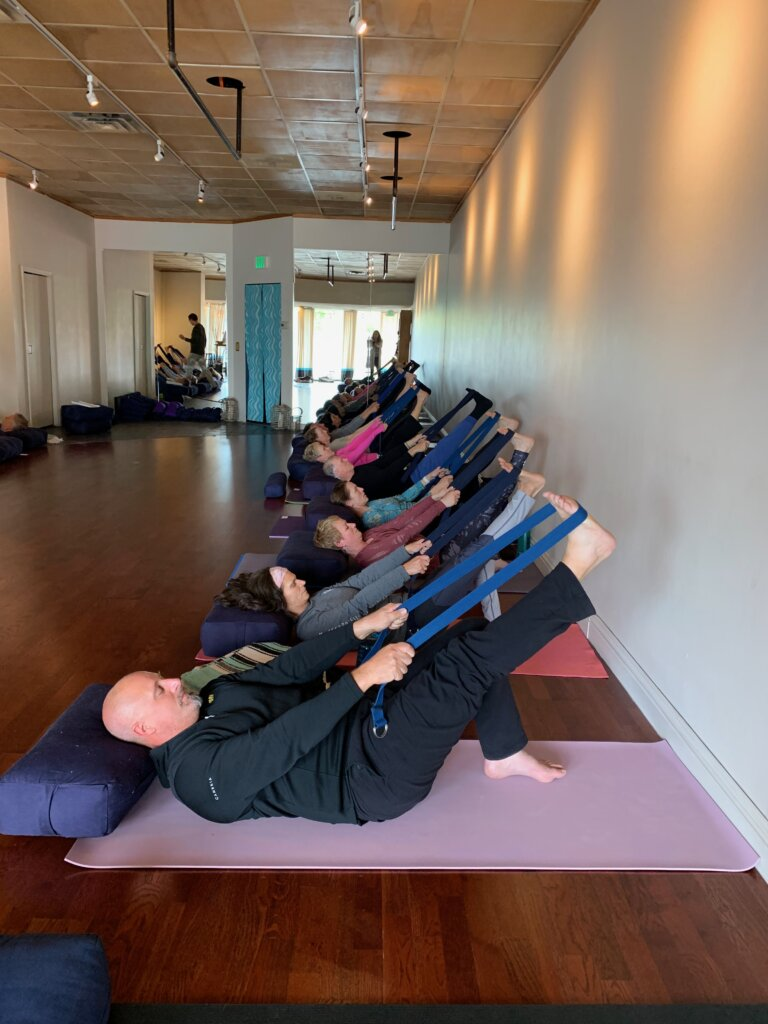 Mixed age class demonstrates Avita Yoga lying supine with strap around right foot and leg extended in the air.