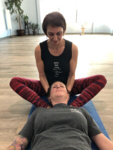 Holly Schramm lengthens woman's neck in savasana.
