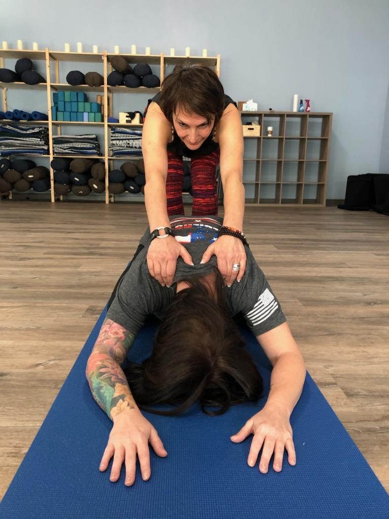 Holly Schramm provides a hands-on assist in Savasanassage child's pose.